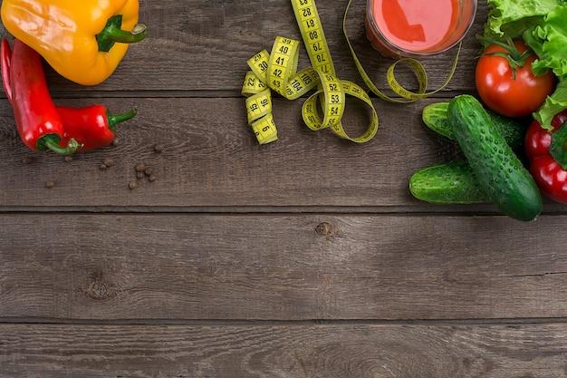 스포츠와 다이어트. 야채, 토마토 주스 한 잔과 센티미터. 고추, 토마토, 소박한 배경에 샐러드. 평면도. 복사 공간