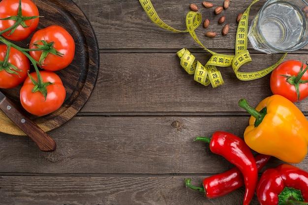 스포츠와 다이어트. 야채와 센티미터. 고추, 토마토, 소박한 배경에 샐러드. 평면도. 복사 공간