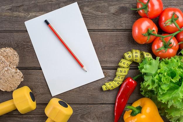 소박한 배경에 스포츠 및 다이어트 야채 아령과 센티미터 고추 토마토 샐러드