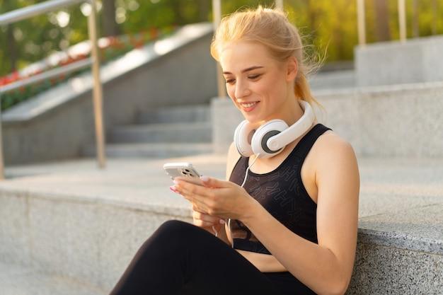 Спорт и фитнес молодая взрослая кавказская женщина с помощью смартфона бетонный пол отдыхает после утренней тренировки на открытом воздухе в летнем парке спортивная девушка отдыхает с помощью мобильного телефона