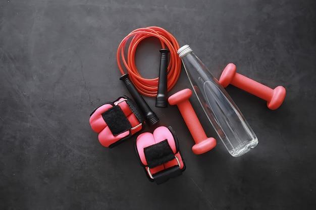 Спорт и здоровый образ жизни. аксессуары для спорта. коврик для йоги с гантелями и скакалка. спортивный фон с концепцией домашних упражнений.