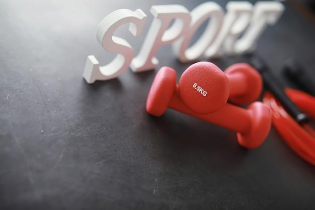 スポーツと健康的なライフスタイル。スポーツ用アクセサリー。ヨガマットダンベルと縄跳び。ホームエクササイズの概念を持つスポーツの背景。