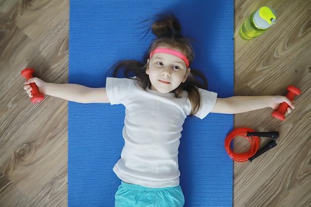 Спорт и здоровый образ жизни. дети, занимающиеся спортом дома. коврик для йоги с гантелями и скакалка. спортивный фон с концепцией домашних упражнений.