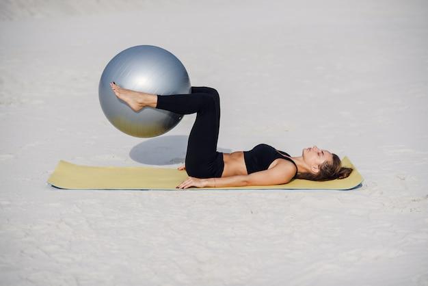 スポーツと健康的なライフスタイルのコンセプト。ビーチでフィットボールで胃の運動を行う美しいフィットネス女の子。ピラティスの演習を行う若い女性。