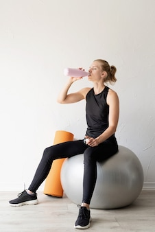 스포츠와 건강한 라이프 스타일 개념입니다. fitball로 운동한 후 물을 마시는 젊은 여성의 초상화