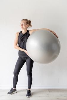 스포츠와 건강한 라이프 스타일 개념입니다. fitball을 들고 웃고 있는 낚시를 좋아하는 젊은 여성의 초상화