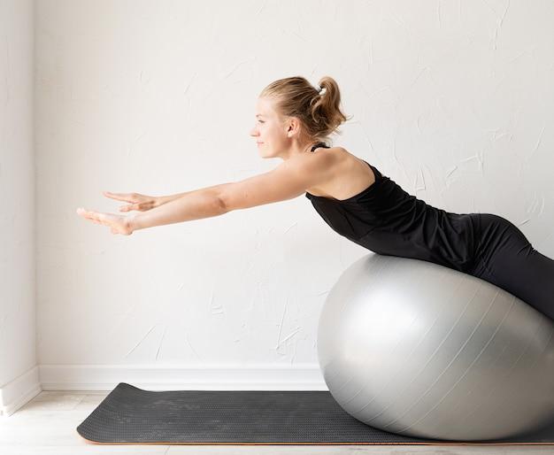 스포츠와 건강한 라이프 스타일 개념입니다. 그녀의 등을 훈련 피트 니스 공에서 운동 하는 젊은 웃는 낚시를 좋아하는 여자