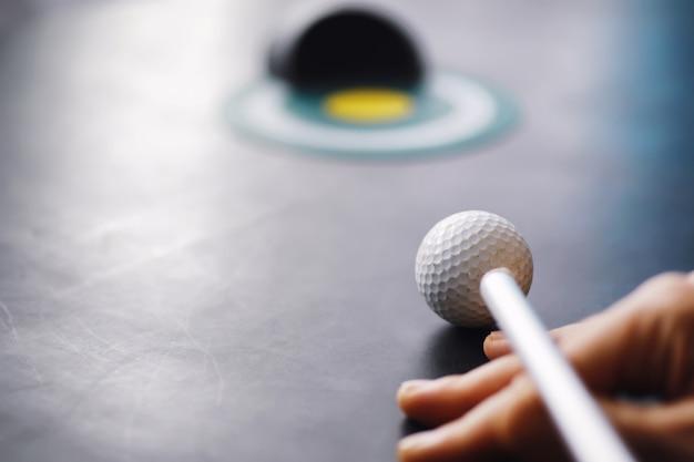Спорт и здоровый образ жизни. мини гольф. белый мяч для гольфа и набор для мини-гольфа на столе. спортивный фон с концепцией гольфа.