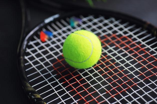 Спорт и здоровый образ жизни. теннис. желтый мяч для тенниса и ракетка на столе. спортивный фон с концепцией тенниса.
