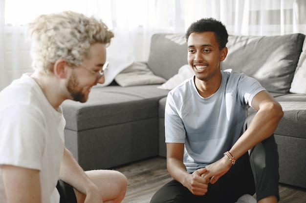 スポーツと健康的な生活。フィットネス トレーナーと研修生がフィットネス マットで話している。男性は床に座ってブログを撮影しています。