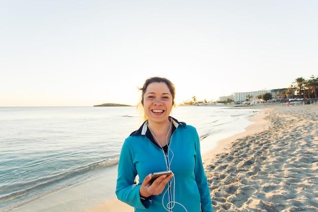 스포츠 및 라이프스타일 개념 - 야외에서 이어폰을 끼고 달리는 여성.