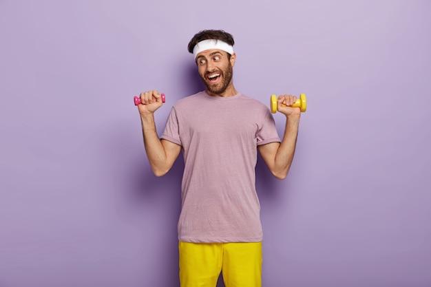 スポーツとレクリエーションのコンセプト。面白いスポーツマンはダンベルで運動し、腕に強い筋肉を持ちたい、カジュアルな紫色のtシャツと黄色のショートパンツを着ています