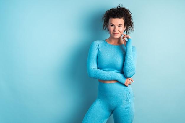스포츠 및 레크리에이션 개념입니다. 파란색 상의와 반바지를 입은 자신감 넘치는 슬림 스포츠우먼은 정기적인 훈련으로 건강한 생활 방식을 주도합니다. 스톡 사진