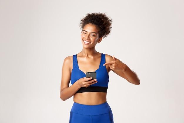 スポーツとテクノロジーのコンセプト。健康で健康なアフリカ系アメリカ人の女性アスリート、カメラでウインクして