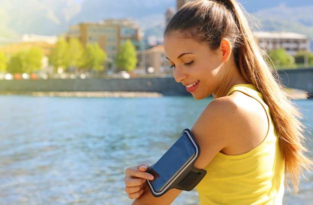 スマートフォン用スポーツアームバンド。ビーチで屋外フィットネストレーニングの前に彼女のスマートフォンに触れるスポーティな女の子。