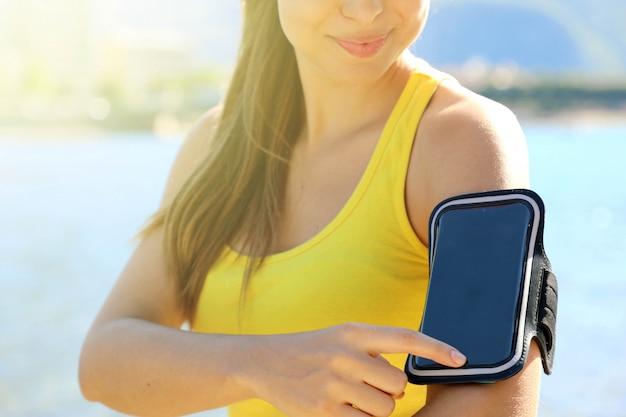 スマートフォン用スポーツアームバンド。ビーチで屋外フィットネストレーニングの前に彼女のスマートフォンに触れるスポーティな女性。