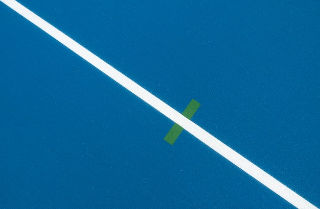 Sport background. blue running track with white lines and green mark in sport stadium. top view