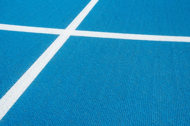 Sport background. blue running track with white lines in sport stadium. top view