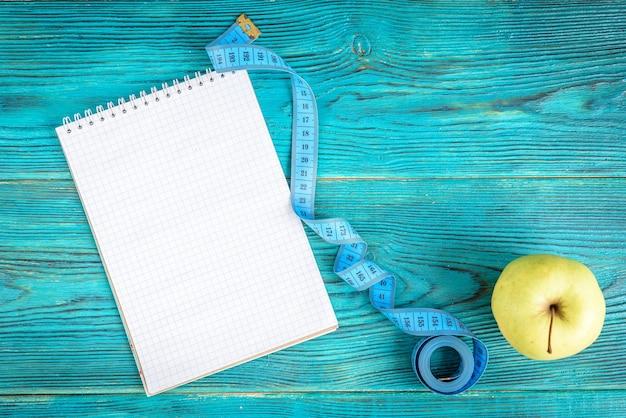 Спортивная фоновая лента, блокнот и яблоко на синем деревянном фоне. фитнес, здоровый образ жизни, план тренировок.