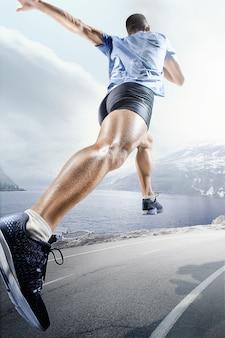 Спортивные фоны. спринтер стартует на беговой дорожке. коллаж. рекламная концепция. спортсмен-мужчина бежит против пейзажа норвегии
