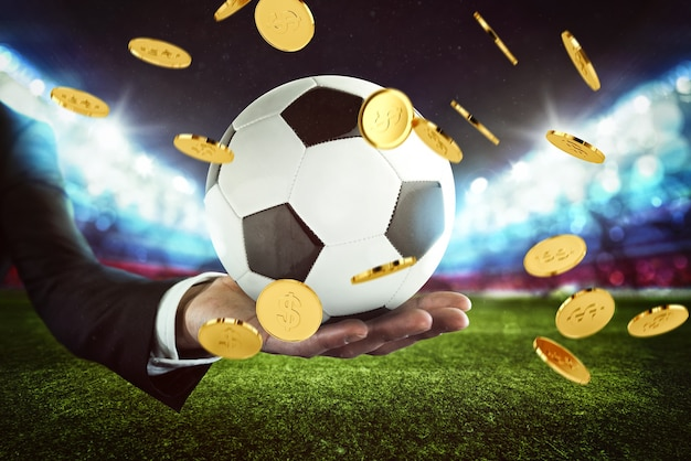 スポーツベッティング。サッカースタジアムでビジネスマンの手によって保持されたサッカーボールのお金の雨
