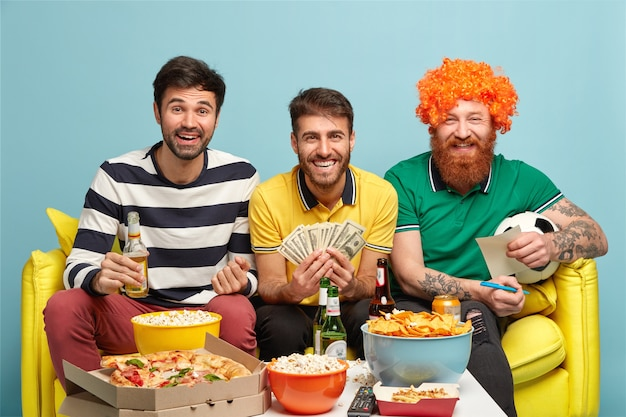 Concetto di scommesse sportive. amici uomini contenti guardano la partita in tv, tengono soldi, pallone da calcio, mangiano pizza, patatine, popcorn