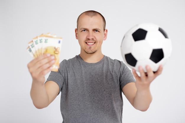 Концепция спорта, ставок, успеха, победы и денег - веселый молодой человек с деньгами в евро и футбольным мячом позирует на сером фоне