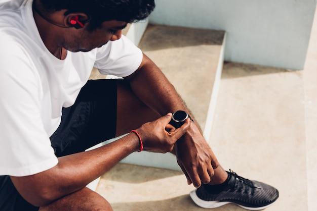Спорт черный мужчина носить современные умные часы он сидит отдыхает перед тренировкой бег