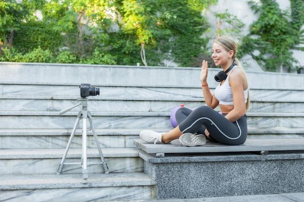 スポーツブログ。魅力的な若いスポーツ女性が屋外でフォロワーに挨拶し、三脚のカメラに記録します。彼女のフィットネスvlogのレッスン