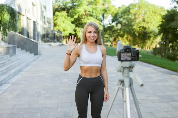 Спортивный блог. привлекательная молодая спортивная женщина приветствует своих последователей на открытом воздухе, записывает на камеру на штативе. урок для ее фитнес-видеоблога
