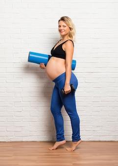 Беременная женщина спорта белокурая делая тренировку внутри помещения с циновкой