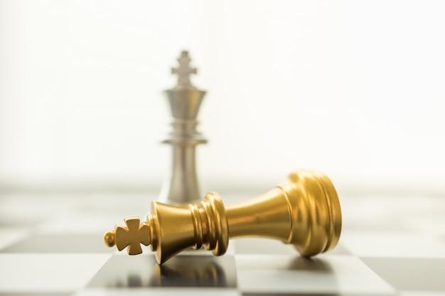 スポーツボードゲーム、ビジネスおよび計画の概念。コピースペースとチェス盤に落下の金と銀のキングチェスの駒のクローズアップ。