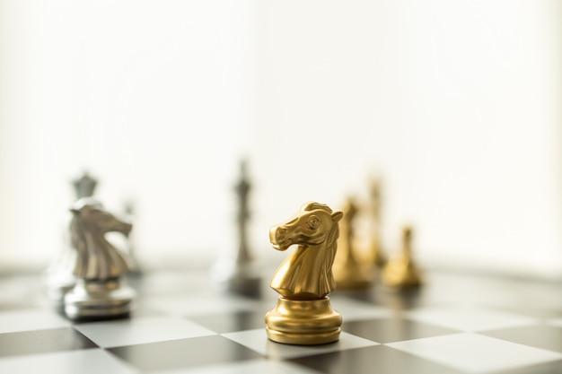 スポーツボードゲーム、ビジネスおよび計画の概念。他の作品とチェス盤の騎士のチェスの駒のクローズアップ。