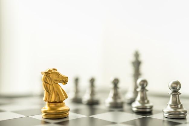 スポーツボードゲーム、ビジネスおよび計画の概念。コピースペースとチェス盤にポーンとキングシルバーの駒に直面する騎士のゴールドチェスの駒のクローズアップ