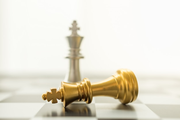 Sport board game, business and planning concept. closeup of falling gold and silver king chess piece on chessboard with copy space.