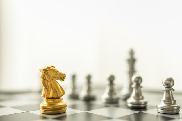 Sport board game, business and planning concept. closeup of knight gold chess pieces face to face with pawn and king silver pieces on chessboard with copy space
