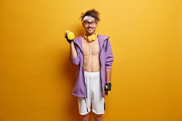 스포츠, 보디 빌딩 및 건강한 라이프 스타일 개념. 쾌활한 동기 부여 남자는 강한 팔을 위해 덤벨을 들어 올리고, 남성의 힘과 근육질의 몸통을 가진 eagers는 활동적인 옷을 입고 노란색 벽에 고립 된