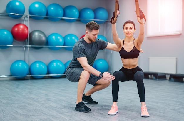 スポーツ、ボディービル、ライフスタイル、人々のコンセプト-ジムでの若い男性と女性のトレーニング。トレーナーとフィットネスの女の子がジムでトレーニングをしています。