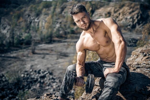 スポーツ、ボディービル、ライフスタイルと人々の概念-バーベルの屈曲筋を持つ若い男。屋外でトレーニングをしているフィットネス男。