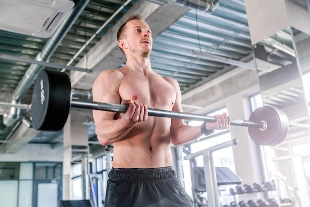 Спорт, бодибилдинг, образ жизни и люди концепции - молодой человек с мускулами штанги в тренажерном зале. горизонтальное фото