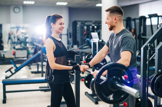 Sport, bodybuilding, lifestyle and people concept - young man and woman with a barbell. trainer and fitness girl are having workout at gym.