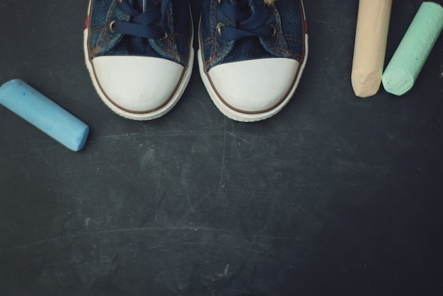 スポーツブーツ子供の教育チョークコピースペースを持つテクスチャ黒板を作ります。