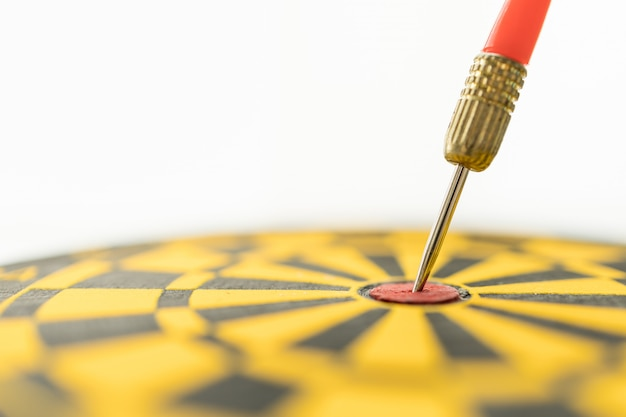 Sport, business, goal, planning and target concept. close up of red darts lace hit on center of black and yellow dart board