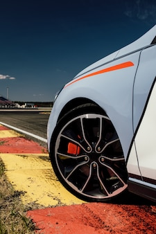 軌道に乗っているスポーツカー。レーストラックでのアスファルト付きのスポーツカーの美しいホイール。