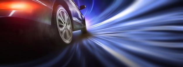 Колесо спортивного автомобиля дрейфует в ночное время на фоне городского освещения
