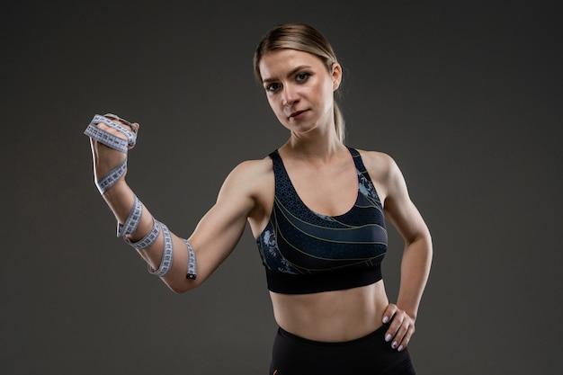 スリムな体型のスポーツ白人少女は黒い背景に分離された演習を行う
