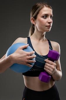 スリムな体型のスポーツ白人少女は黒い背景に分離された青いボールで演習を行う