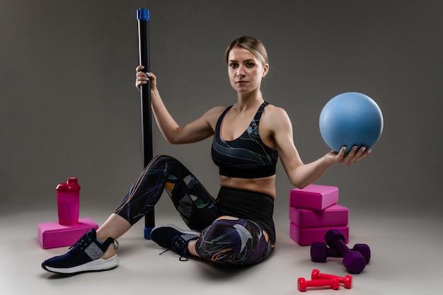 スリムな体型のスポーツ白人少女は黒い壁に分離された様々なスポーツ用品で演習を行う