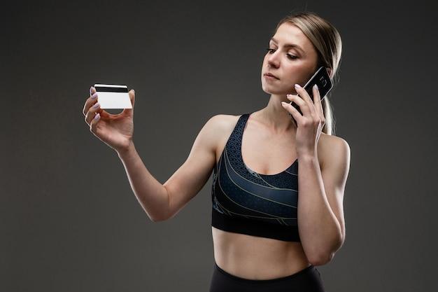 スリムな体型のスポーツ白人の女の子は、黒の背景に隔離された時間内に正しく食べることをお勧めします