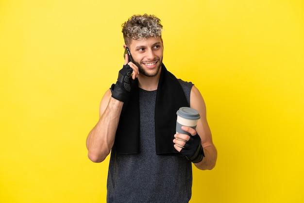 노란색 배경에 격리된 스포츠 백인 남자는 테이크아웃 커피와 모바일을 들고 있습니다.